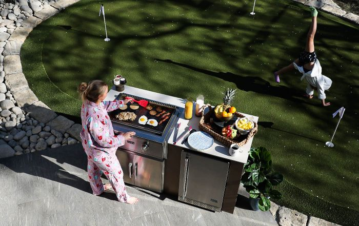 Woman Cooking on Coyote's Flat Top Grill